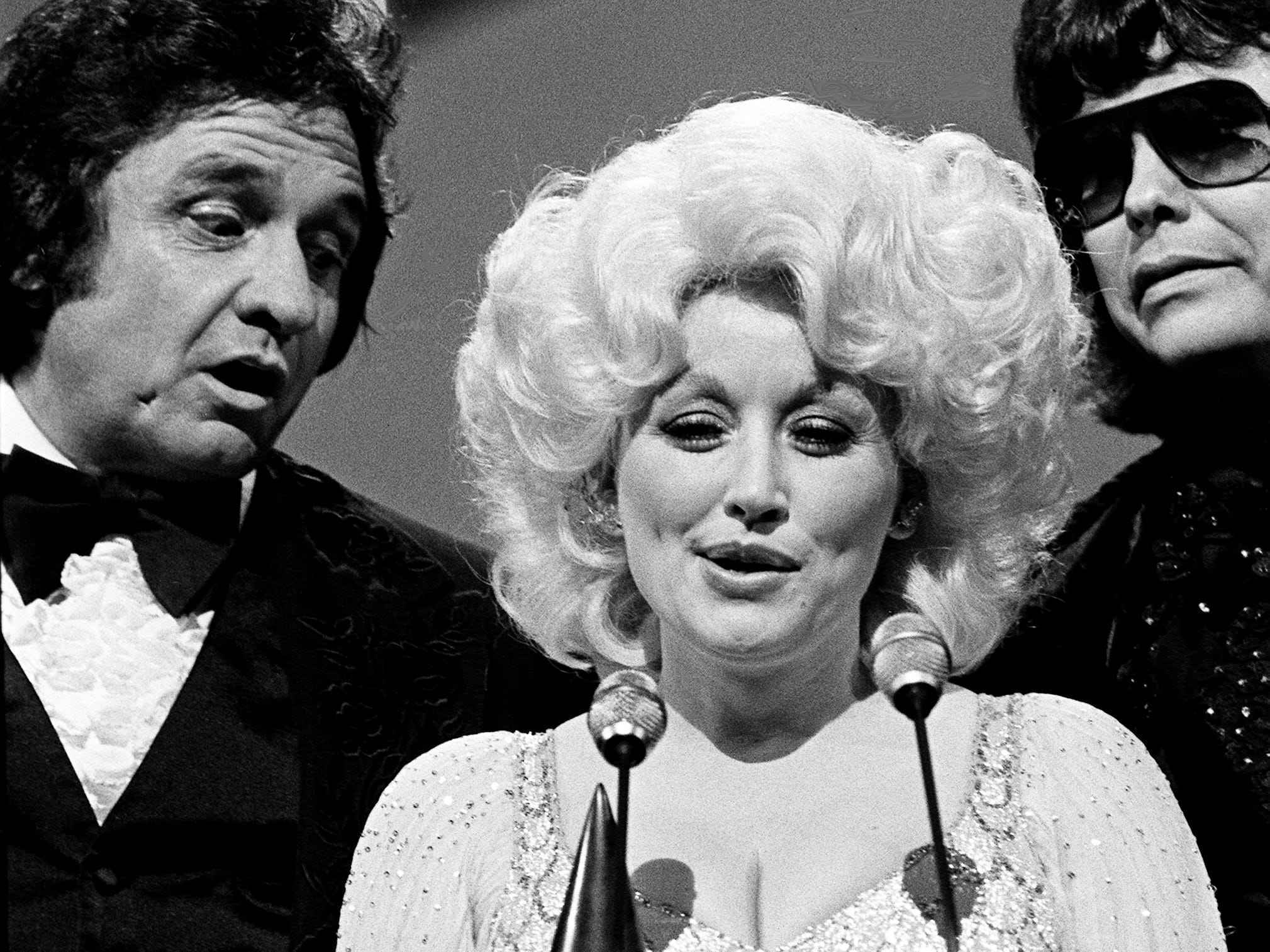 Dolly Parton speaks after winning the Entertainer of the Year award during the 12th annual CMA Awards show at the Grand Ole Opry House on Oct. 9, 1978. Standing by are presenters Johnny Cash, left, and Ronnie Milsap.