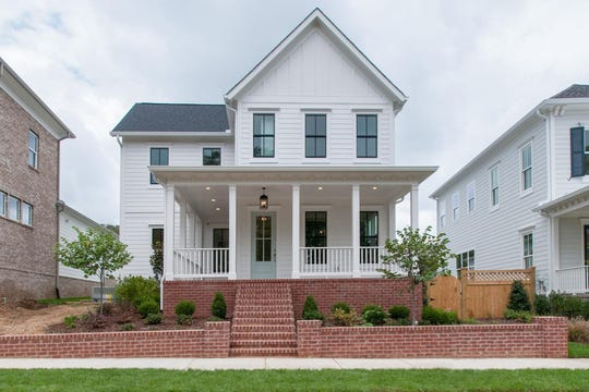 This home in the Westhaven community is Southern Land Homebuilding's take on the popular white farmhouse trend with unique touches such as the brick foundation and colored front door.