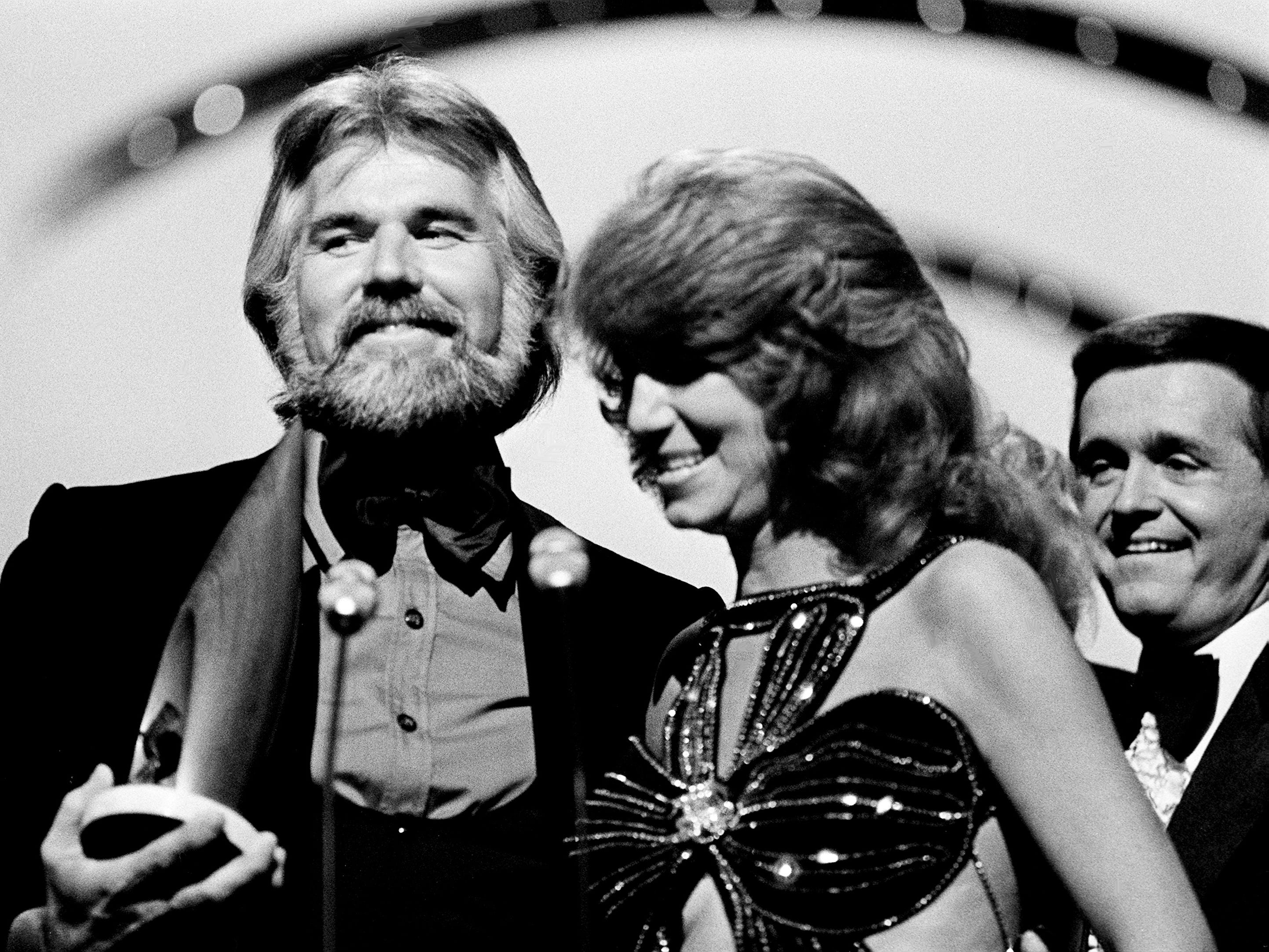 Kenny Rogers and Dottie West accept their Vocal Duo of the Year award during the 12th annual CMA Awards show at the Grand Ole Opry House. Looking on is presenter Bill Anderson, right.