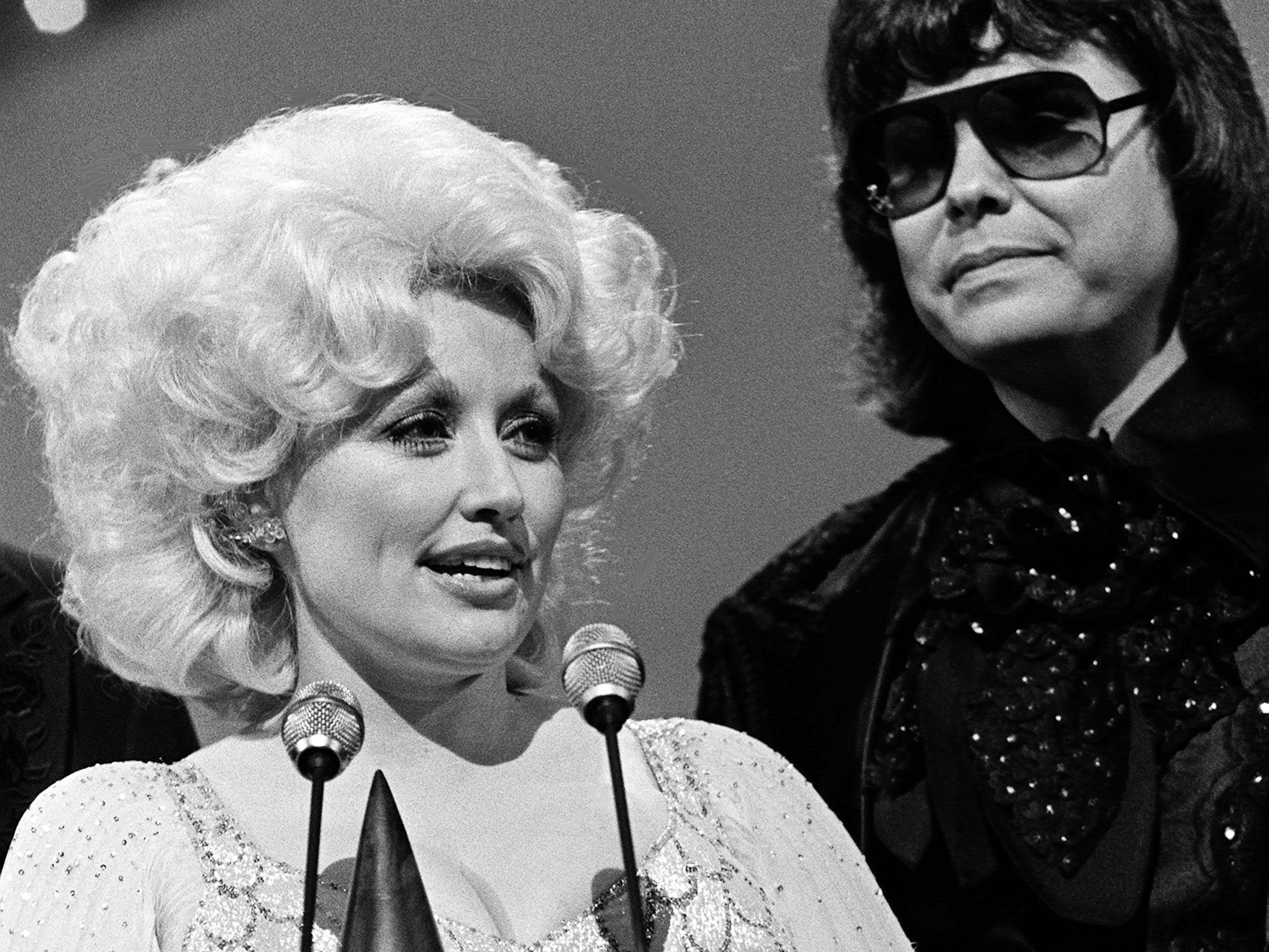 Dolly Parton speaks after winning the Entertainer of the Year award during the 12th annual CMA Awards show at the Grand Ole Opry House on Oct. 9, 1978. Standing by is presenter Ronnie Milsap.