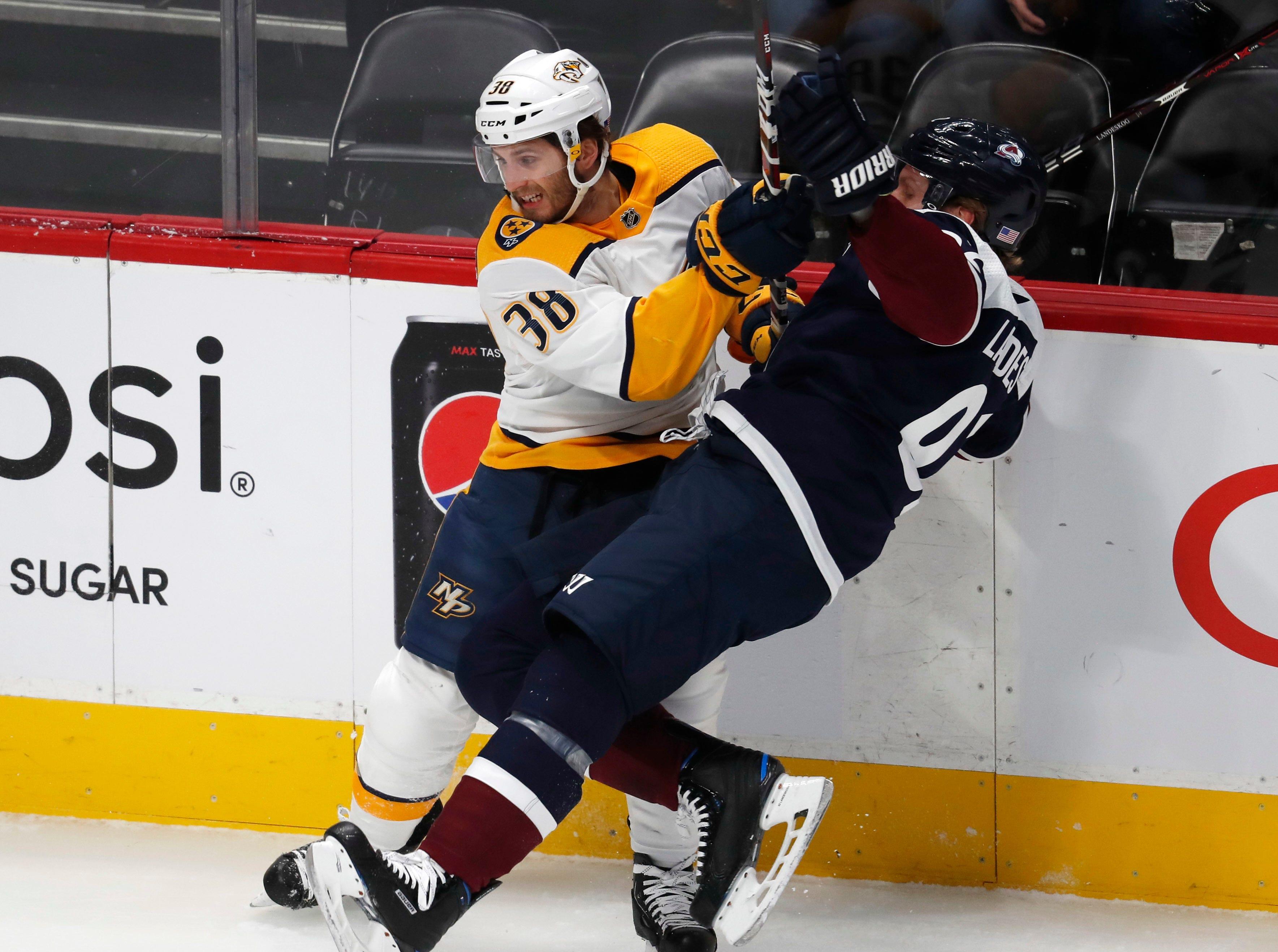 Nashville Predators right wing Ryan Hartman, left, checks Colorado Avalanche left wing Gabriel Landeskog in the first period of an NHL hockey game Wednesday, Nov. 7, 2018, in Denver.