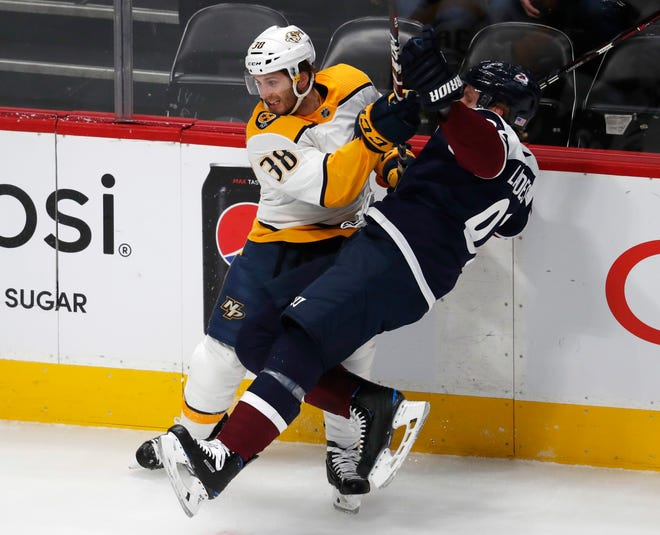 Nashville Predators right wing Ryan Hartman, left, checks Colorado Avalanche left wing Gabriel Landeskog in the first period of an NHL hockey game Wednesday.