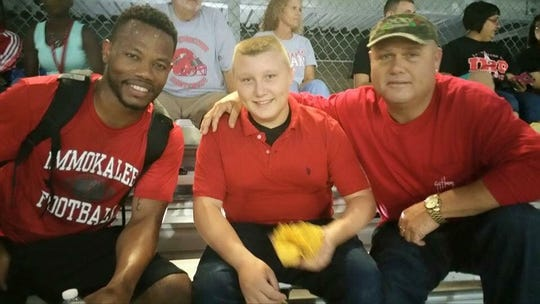 Immokalee High School defensive backs coach Louis Gachette, left, felt a profound loss when Casey Cheney Sr., right, was killed in September. Cheney, shown here with Gachette and his son Casey Jr., was Gachette's godfather and never missed a home game when Gachette played at USF.
