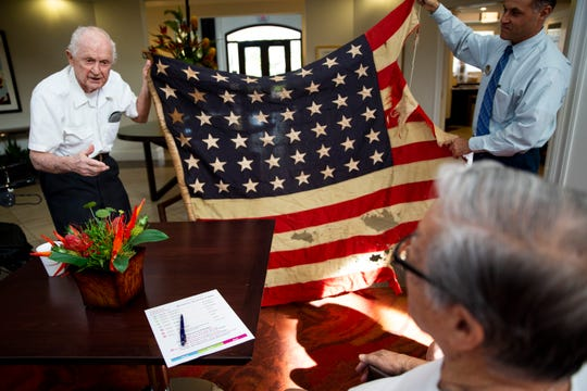 Earl Page, left, who served as a petty officer first class in the Navy during World War II, holds up a flag that flew on his ship during a typhoon with the help of Bill Diamond, right, on Wednesday, Nov. 7, 2018, at The Carlisle in Naples. Page dropped out of high school to enlist in the Navy instead of waiting to be drafted.
