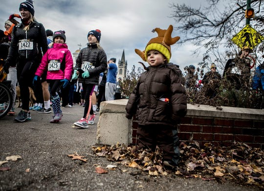Ward Porch, 18 months, dances and watches as people gather before the official start of the 2017 Granville Turkey Trot.