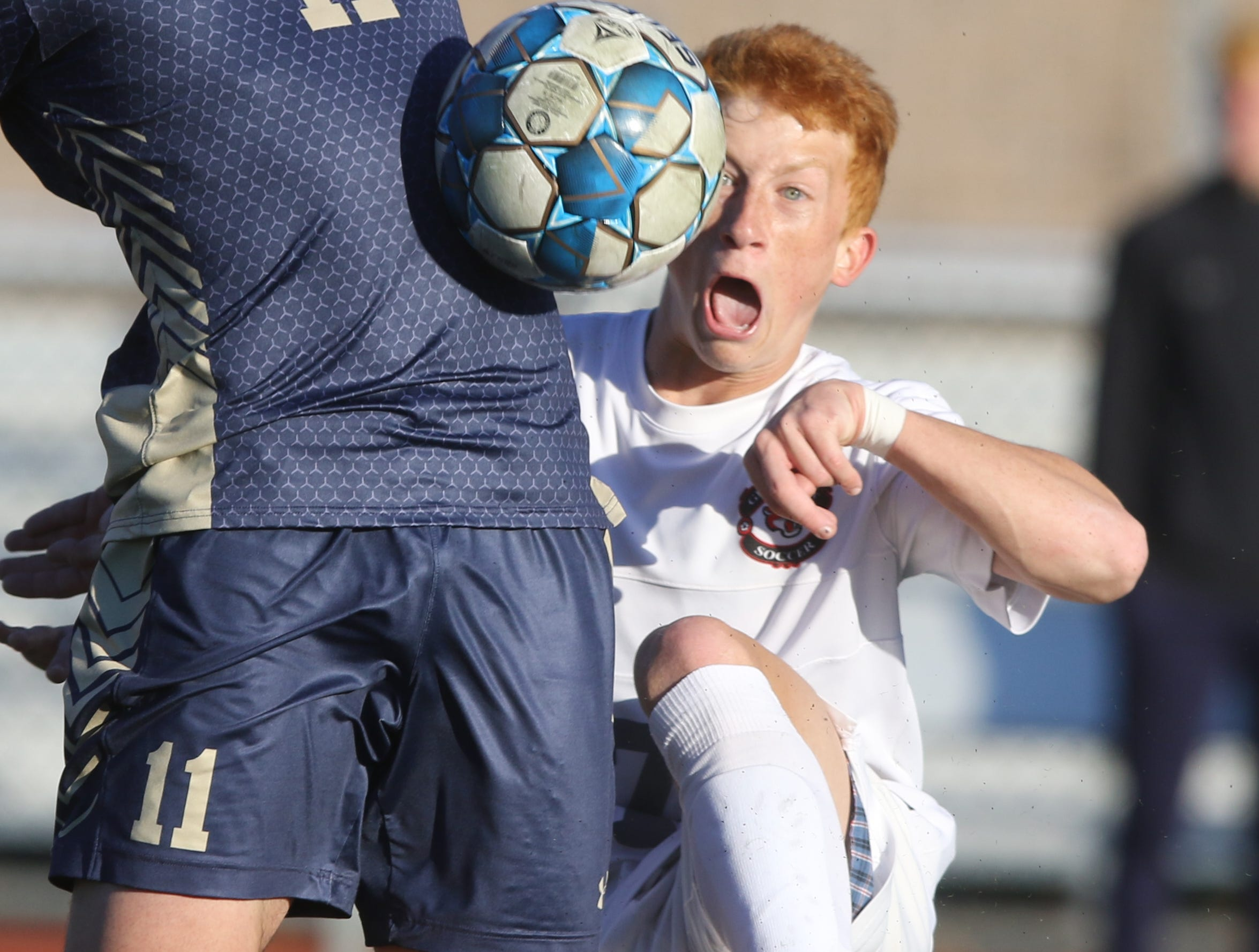 Ben Zakowski heads the ball in the second half while being defended by Brendan Bussiere.