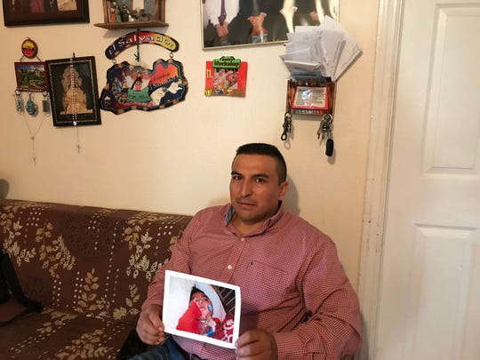 Angel Ojeda, 40, sits in his living room in Belleville surrounded by pictures of his son Angel, who is among the children who contracted the andnovirus at a Wanaque long-term care facility. His son is recuperating at the center, he said.