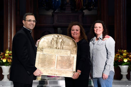 (L-R) Rev. Msgr. Geno Sylva, Mary Feenan and her daughter Mary Nesnay hold the World War I plaque that bears Feenan's great-uncle's name among others lost in the war from St. John's Parish on Thursday, Nov. 8, 2018, in Paterson. The plaque had been put into storage during renovations in the 1980's and was just recently found again.