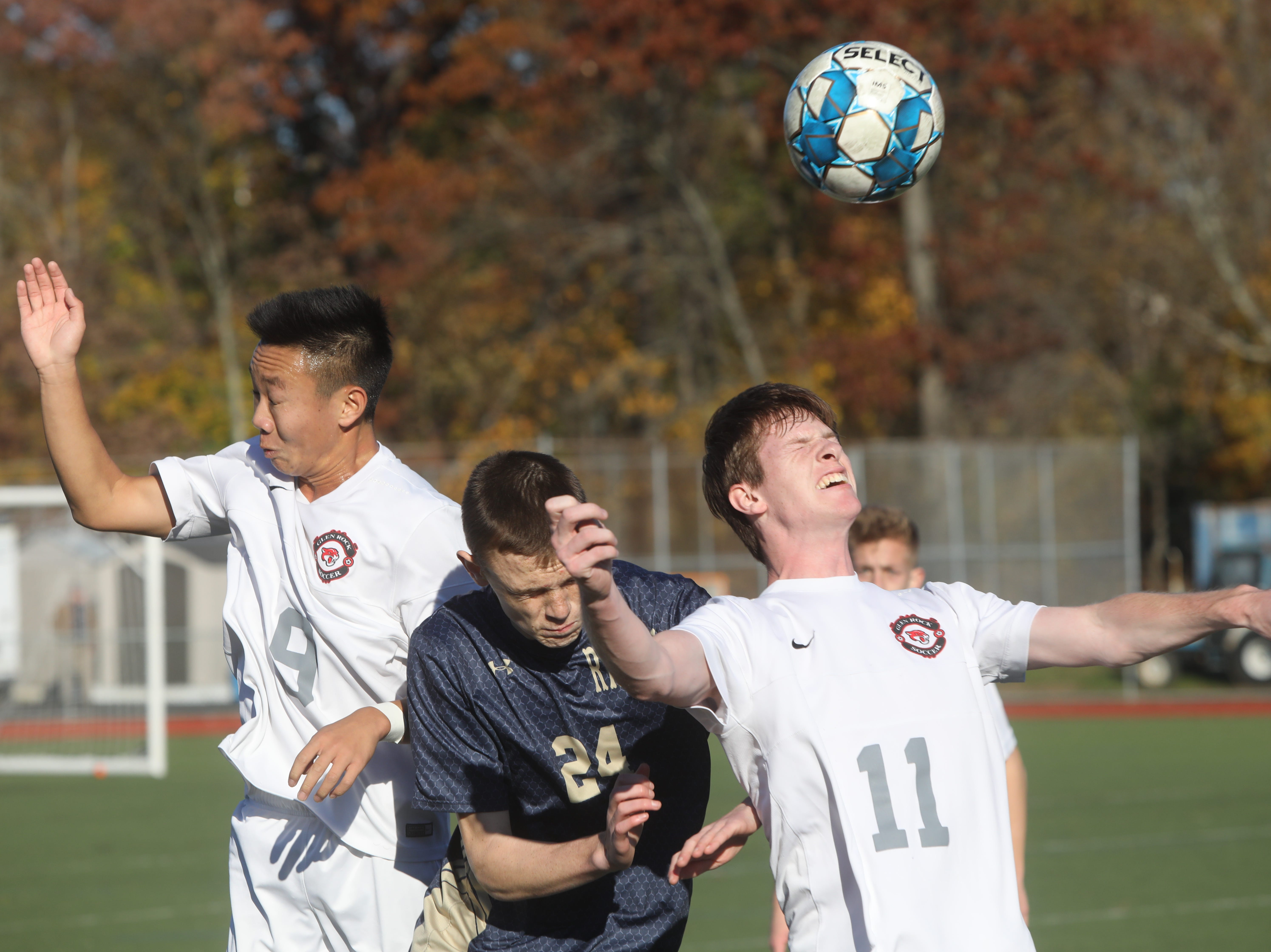Josh Kim and John Corry of Glen Rock keep the ball from Aidan Hildebrand of Ramsey.