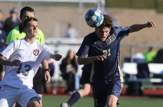 Connor Daly watches as Brian Miller of Ramsey heads the ball.