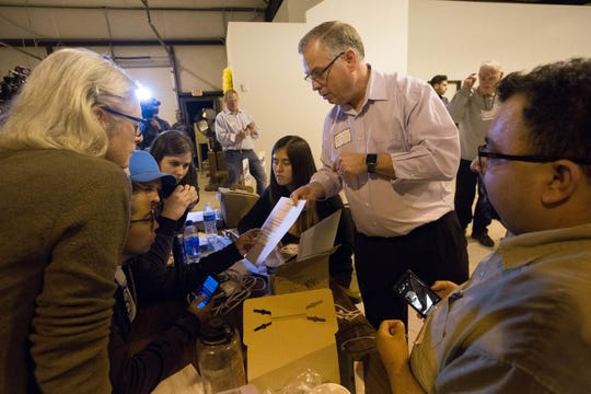 Daniel A. Ivey-Soto, right, Executive Director of New Mexico County Clerks Affilates and a representative from District 15, shows preliminary absentee ballot totals to Chris Schaljo, chair of the Doña Ana County Democrats and others seated around a table at the Doña Ana County Bureau of elections Warehouse on Nov. 7, 2018.