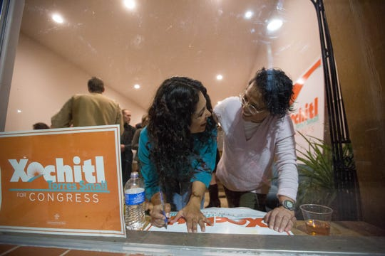 Xochitl Torres Small signs a campaign sign for Graciela Unguez, right, during a celebration after Torres Small received word that absentee ballots had pulled the Congressional District 2 Race in her favor, Wednesday November 7, 2018.