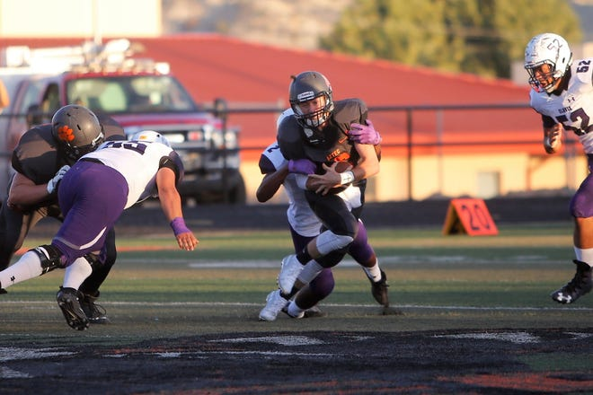 Aztec quarterback Zach Taylor fights for extra rushing yards against Clovis on Aug. 31 at Fred Cook Stadium in Aztec. Taylor ran for 576 yards in his last four games and has 833 rushing yards entering Saturday's 4A playoff opener at Ruidoso.