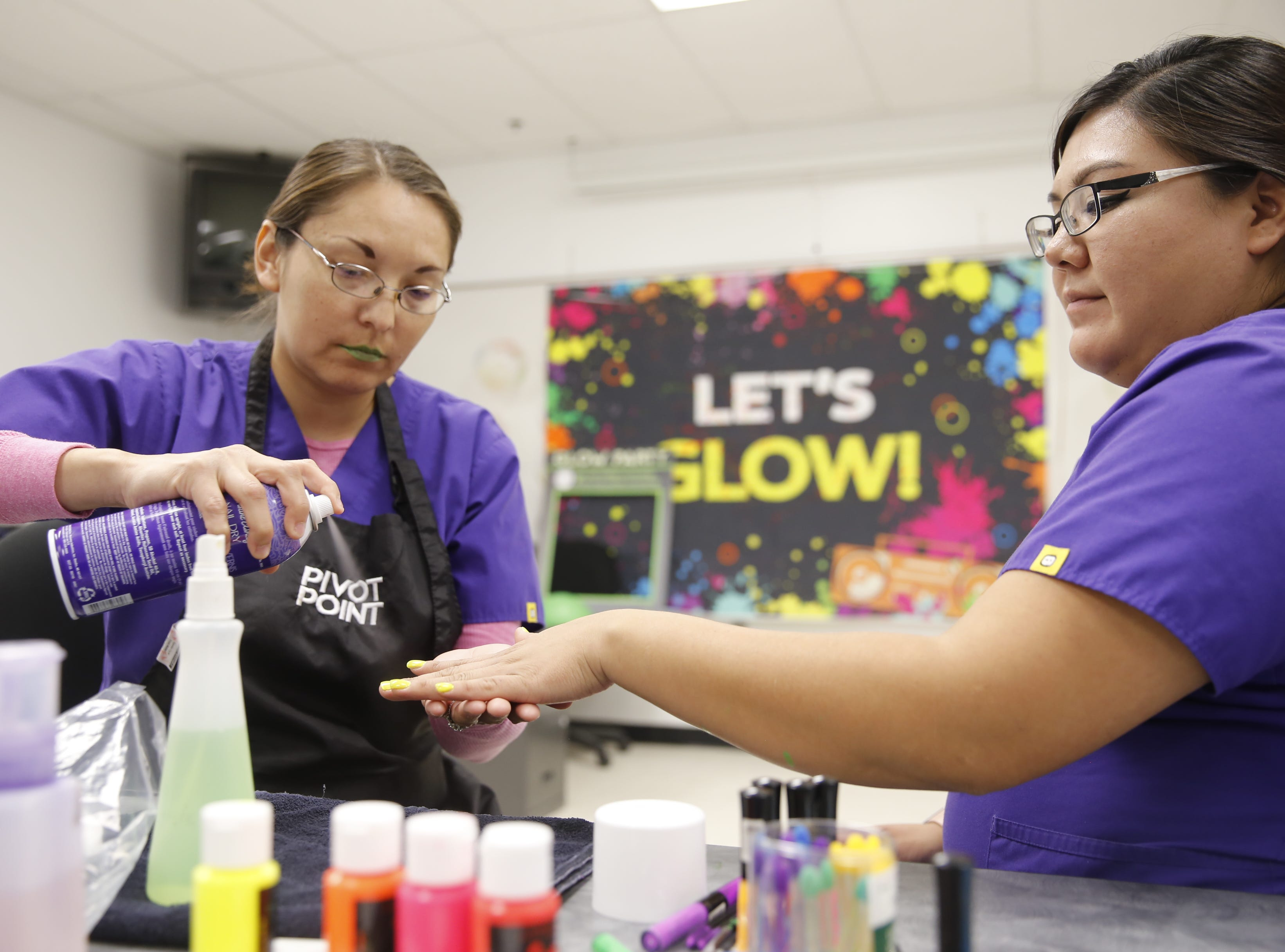 San Juan College cosmetology students Elaine Nelson and Tasheena Halwood, from left, practice their cosmetic skills on Thursday in preparation for the program's Glow Dance Party.