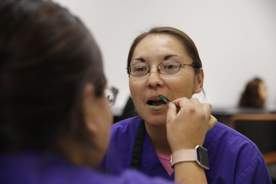 San Juan College cosmetology student Elaine Nelson has glow in the dark lipstick applied to her lips on Thursday.
