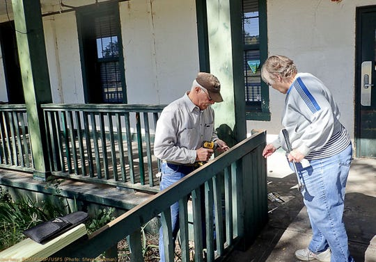 Volunteers Brenda and Dan Wray help repair a bannister leading into the Bureau of Land Management Fort Stanton - Snowy River Cave National Conservation Area headquarters on the Fort Stanton Quadrangle.