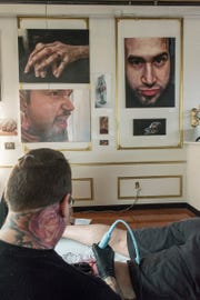 The walls of the tattoo studio and art gallery display oil paintings by Kowaleski, including self portraits.