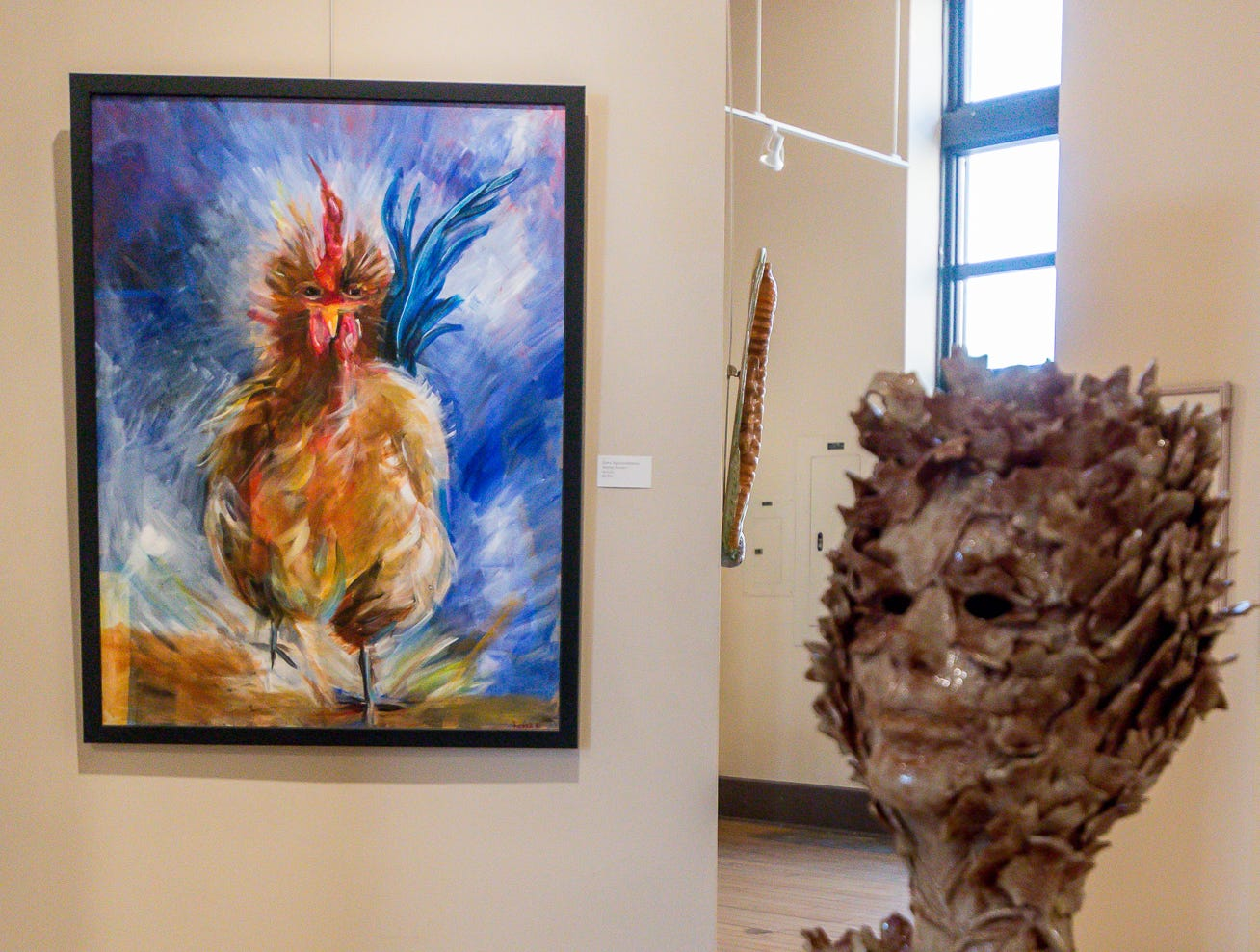 "Kerra Nguyen-Hartman's painting ""Raging Rooster"" looks out toward Robert Logan's ceramic sculpture ""Leaf-Peep Show"" during the ""Cinco Banderas Collection"" display at the Artel Gallery on Tuesday, October 30, 2018. The exhibit, which runs through November 30, is celebrating its 30th anniversary this year."