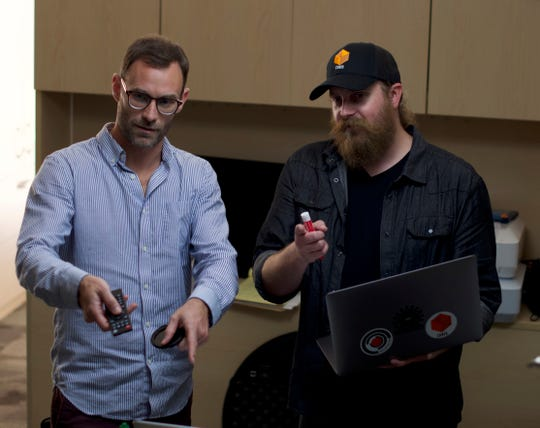 Ryan O'Keeley, left, and Evan Levin work on the technical production for the cubes and the tower for CUBED: Luminous.