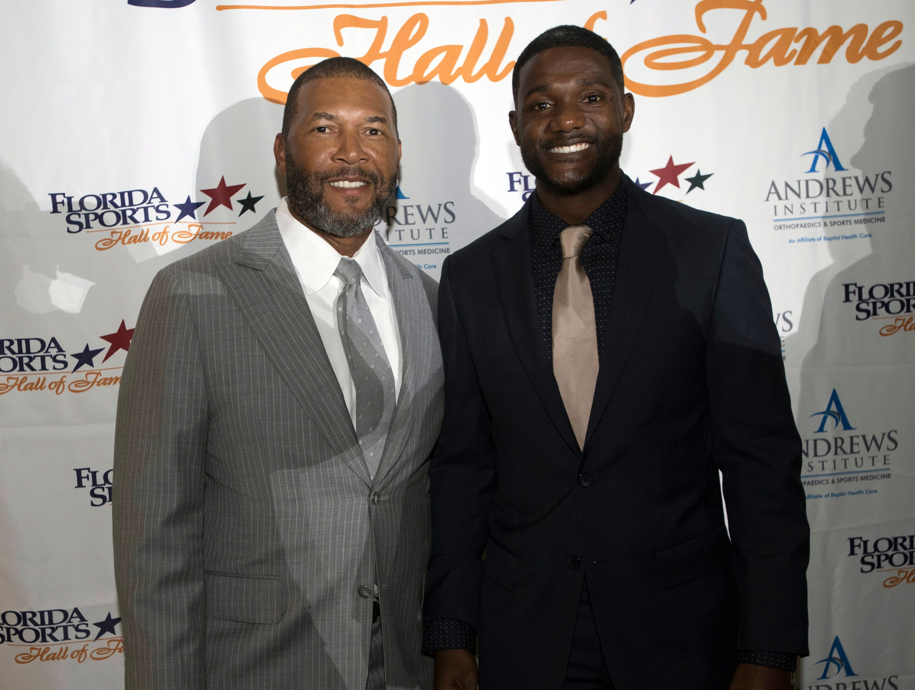 Gary Sheffield and Justin Gatlin, pose for photographs before the start of Wednesday night's 2018 Florida Sports Hall of Fame Enshrinement Ceremony at the National Naval Aviation Museum.