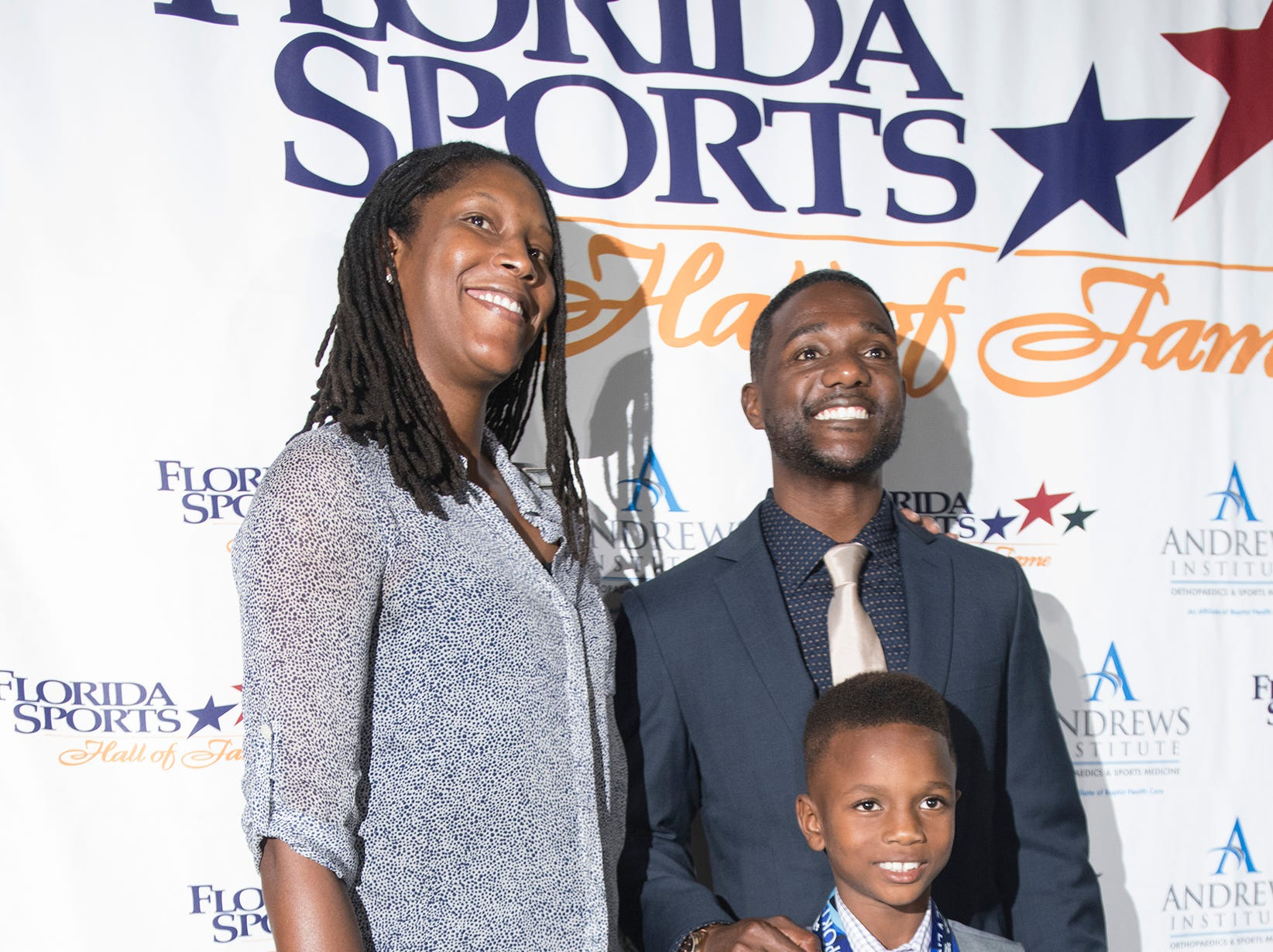 Pensacola own, Michelle Snow and Justin Gatlin, poses for photographs with Pensacola's newest star, 8-year-old Cam Ron Chandler, before the start of Wednesday night's 2018 Florida Sports Hall of Fame Enshrinement Ceremony at the National Naval Aviation Museum.