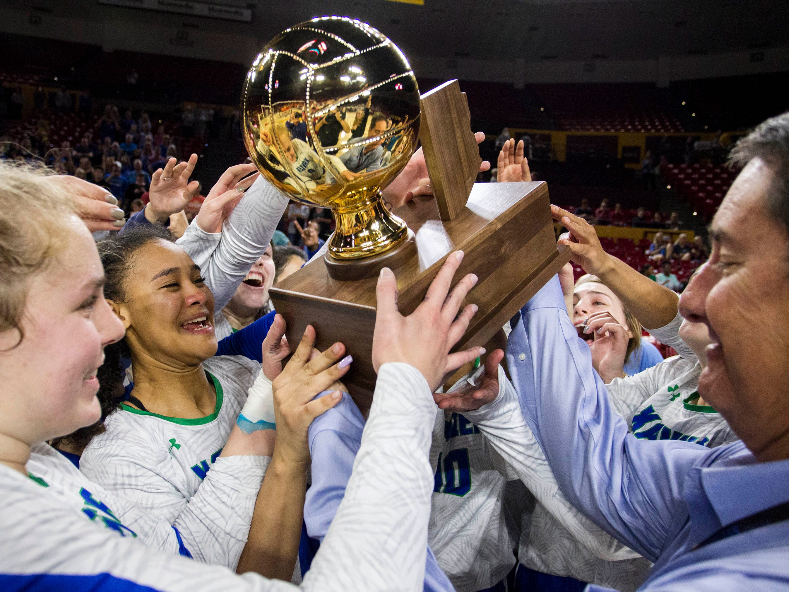 Xavier players can't wait to get their hands on the trophy after their three set win over Corona del Sol in the girls 6A volleyball state championship at Wells Fargo Arena in Tempe, Wednesday, Nov. 7, 2018.