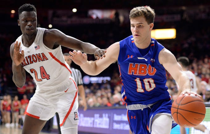 Nov 7, 2018; Tucson, AZ, USA; Houston Baptist Huskies guard Ty Dalton (10) dribbles the ball past Arizona Wildcats guard Emmanuel Akot (24) during the first half at McKale Center. Mandatory Credit: Casey Sapio-USA TODAY Sports