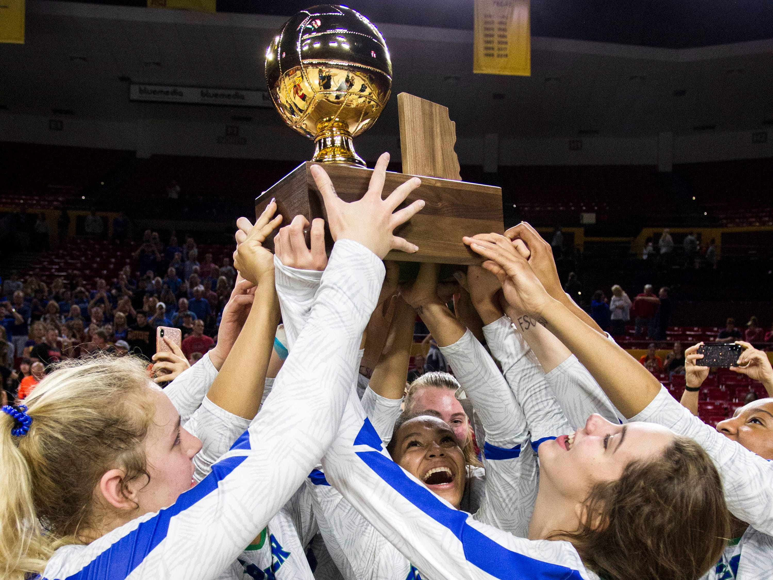 Xavier players host the 6A volleyball trophy in the air after their three set win over Corona del Sol in the volleyball state championship at Wells Fargo Arena in Tempe, Wednesday, Nov. 7, 2018.