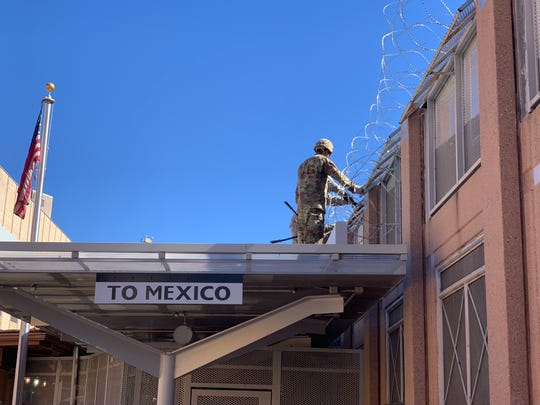 U.S. Army soldiers deployed to the Arizona border string barbed wire atop the Morley pedestrian crossing in downtown Nogales on Nov. 7, 2018.