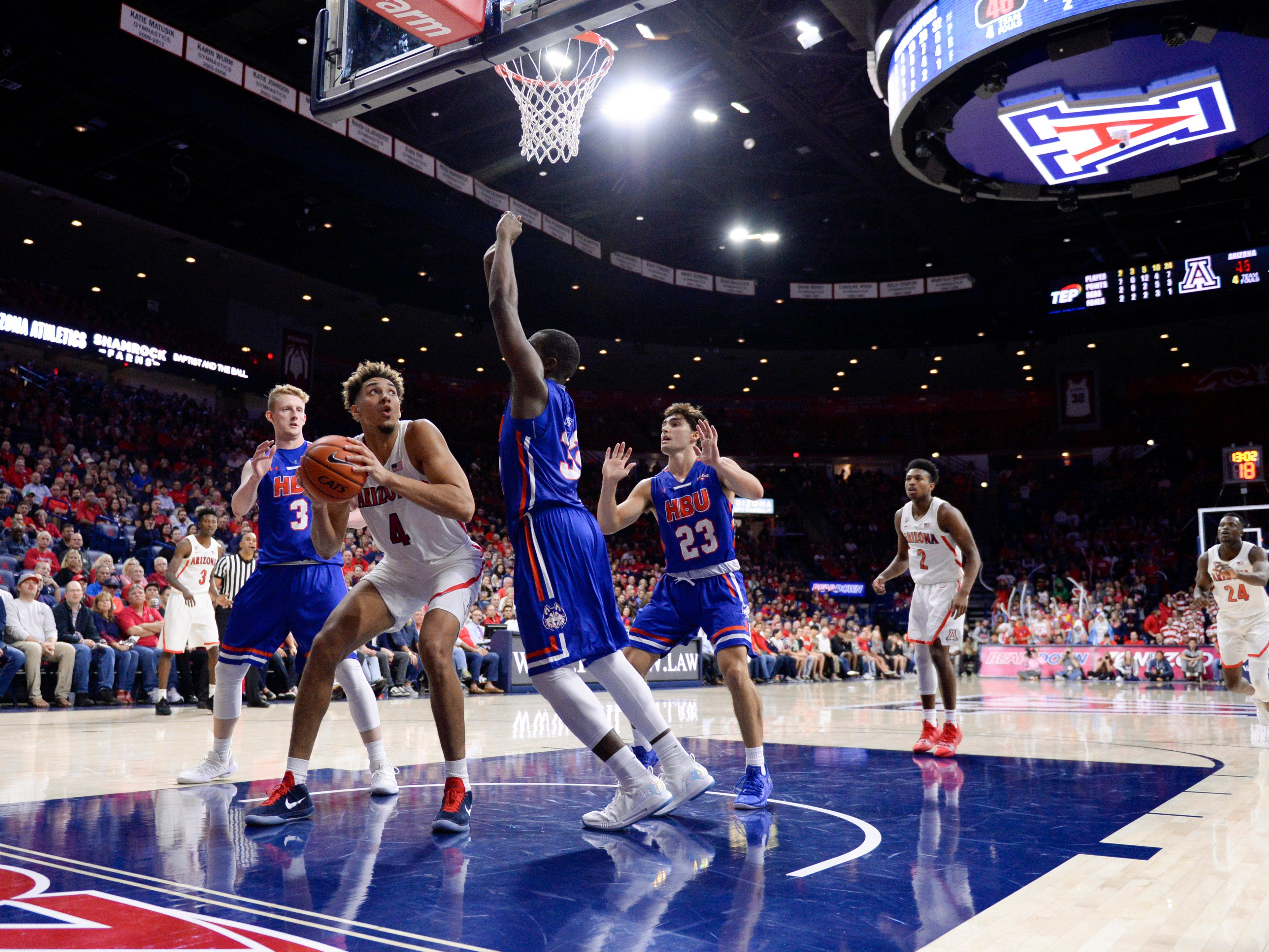 Nov 7, 2018; Tucson, AZ, USA; Arizona Wildcats center Chase Jeter (4) shoots the ball as Houston Baptist Huskies forward Jackson Stent (3) forward Benjamin Uloko (32)  and guard Oliver Lynch-Daniels (23) defend during the second half at McKale Center. Mandatory Credit: Casey Sapio-USA TODAY Sports