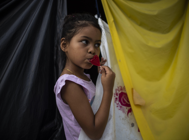 Una niña hondureña que forma parte de la caravana degusta una paleta de corazón, muy populares en México.