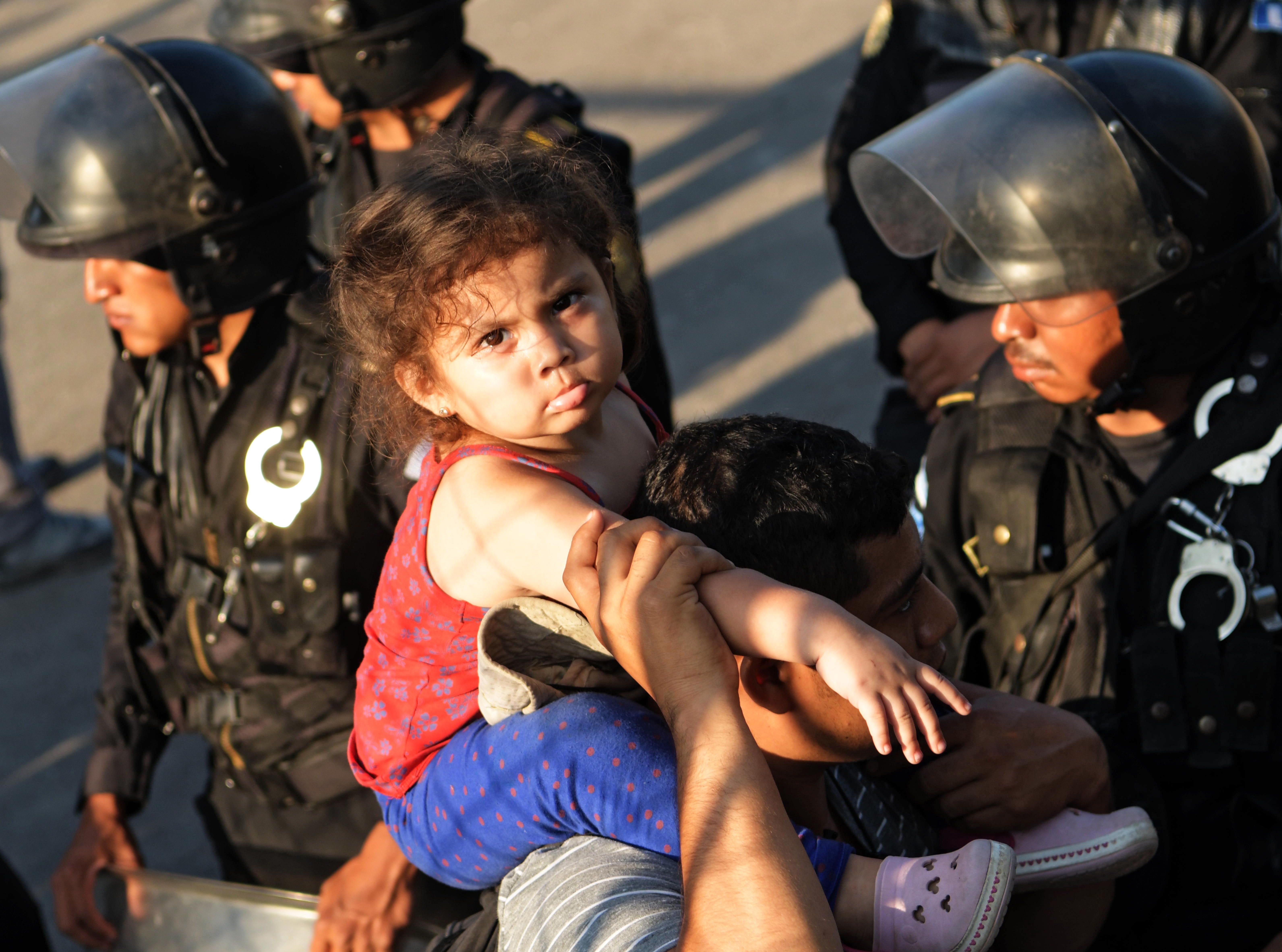 Una niña salvadoreña montada en los hombros de su padre, intenta sortear una barrera de policías en la frontera entre Guatemala y México. Estos son los rostros de los migrantes centroamericanos que huyen de la pobreza y violencia que se vive en sus países; y que por medio de una caravana caminan cientos de kilómetros cruzando ciudades, ríos, carreteras, bosques y fronteras, con el firme propósito de hacer realidad su sueño de llegar a los Estados Unidos.
