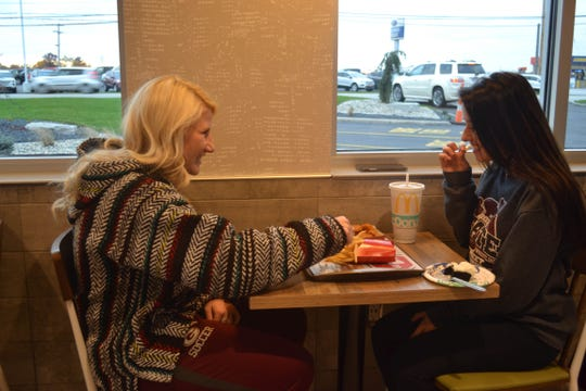 Alayna Nyler, left, of Genoa, and Samara Contos of Toledo enjoy a meal during the Genoa McDonald's grand reopening. Nyler said the newly remodeled interior creates a more welcoming atmosphere.