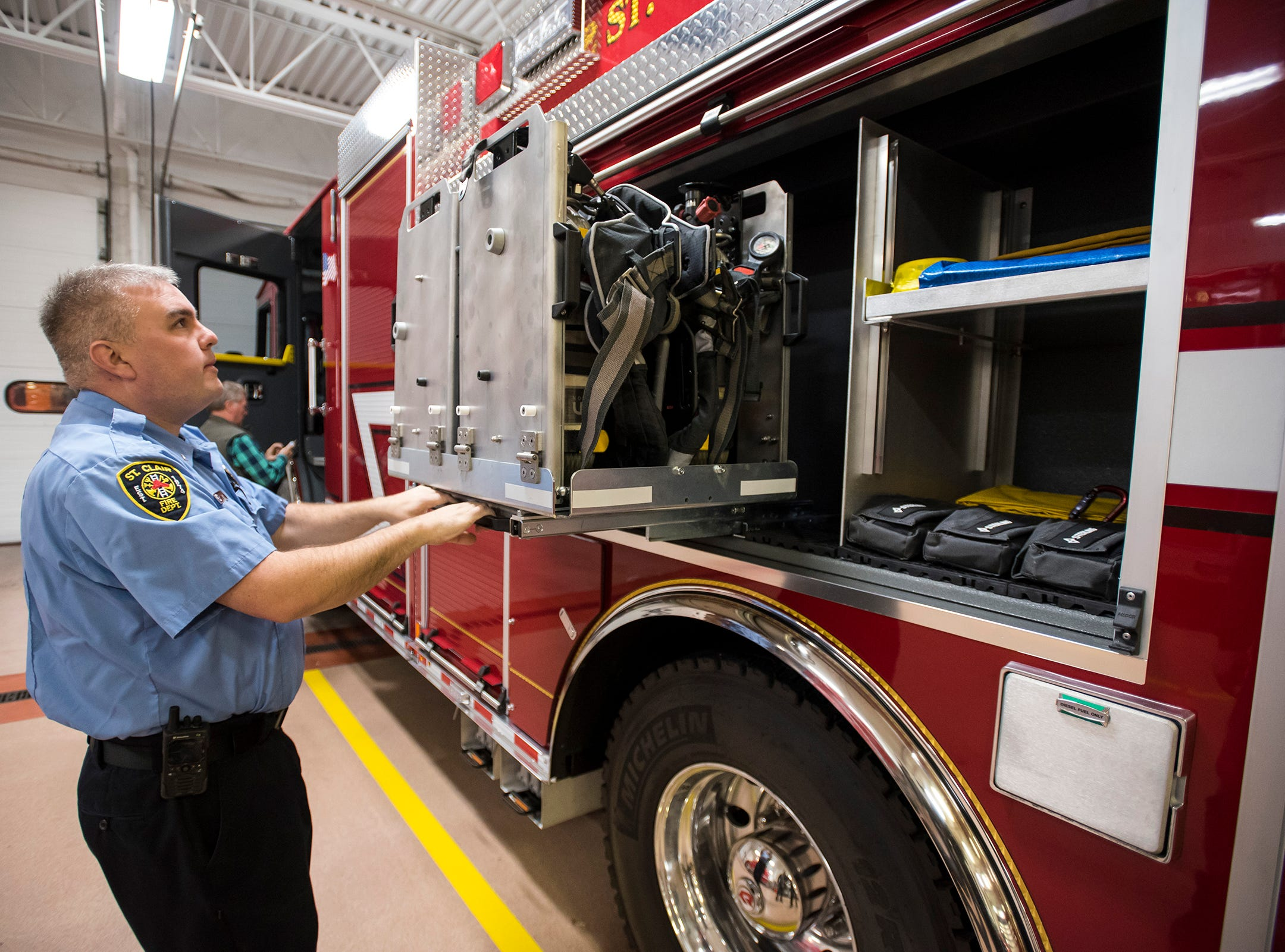 St. Clair Fire Department Lt. Nicholas Chavez slides a rack holding air tanks out of the side of the department's new truck Wednesday, Nov. 7, 2018 at the fire station. Some of the regular gear stored on the truck can be deployed with improvements, such as a slide-out rack containing air tanks that can be pulled directonly onto a standing firefighter's back.