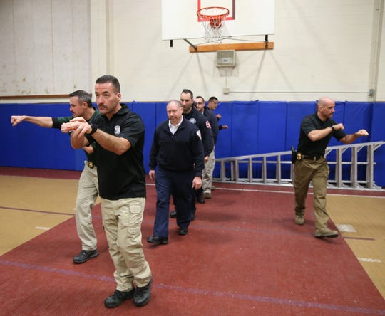 A group of Town of Poughkeepsie police officers lead by officer Joe Lombardi escort a group of paramedics from Arlington and Fairview Fire Districts during an active shooter training session in the Town of Poughkeepsie on November 8, 2018.