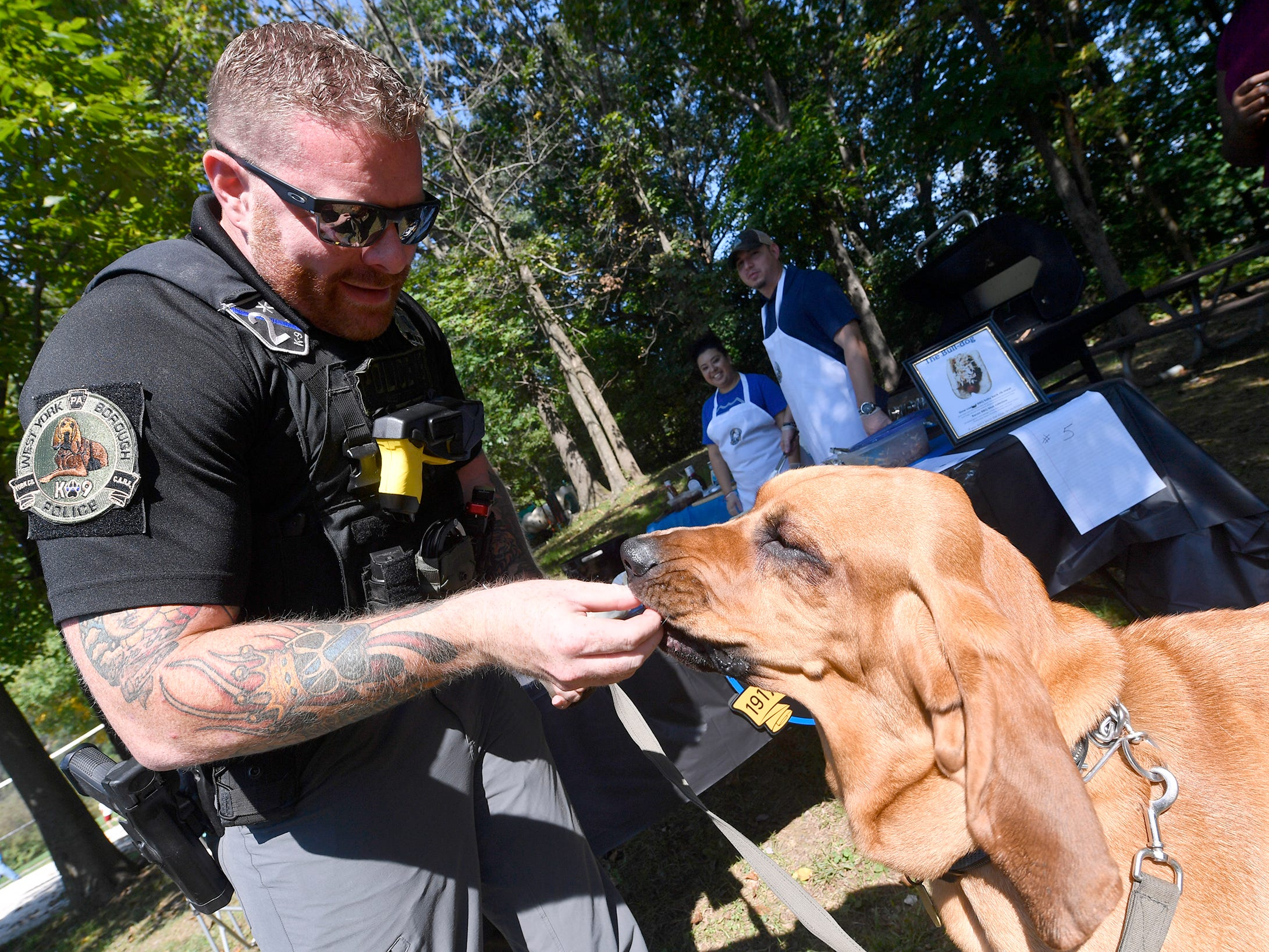Detective Prince gets a hotdog sample from partner Scott Musselman of West York Borough Police as area law enforcement agencies take part in the first annual Top Dog Hotdog Contest, Sunday Oct. 7, 2018. John A. Pavoncello photo