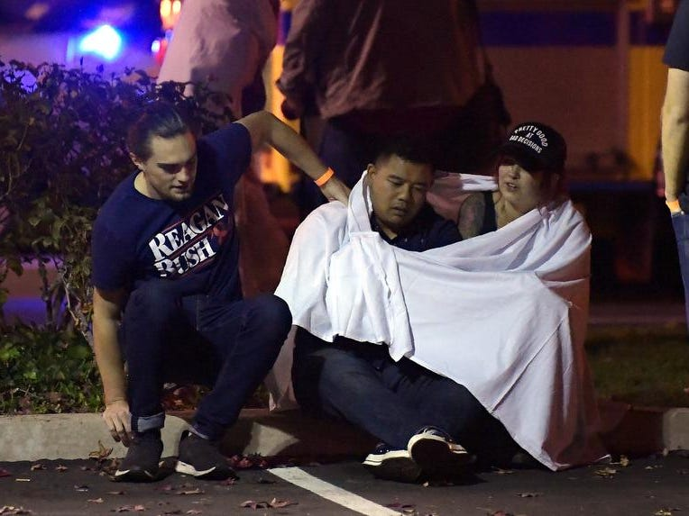 "People comfort each other as they sit near the scene Thursday, Nov. 8, 2018, in Thousand Oaks, Calif. where a gunman opened fire Wednesday inside a country dance bar crowded with hundreds of people on ""college night,"" wounding 11 people including a deputy who rushed to the scene. Ventura County sheriff's spokesman says gunman is dead inside the bar. (AP Photo/Mark J. Terrill)"