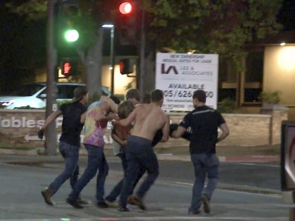 "In this image taken from video a victim is carried from the scene of a shooting, Wednesday evening, Nov. 7, 2018, in Thousand Oaks, Calif.  A hooded gunman dressed entirely in black opened fire on a crowd at a country dance bar holding a weekly ""college night"" in Southern California, killing multiple people and sending hundreds fleeing including some who used barstools to break windows and escape, authorities said Thursday. The gunman was later found dead at the scene.  (RMG News via AP)"