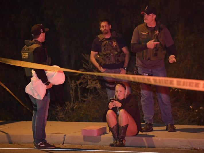 "Sheriff's deputies speak to a potential witness as they stand near the scene Thursday, Nov. 8, 2018, in Thousand Oaks, Calif. where a gunman opened fire Wednesday inside a country dance bar crowded with hundreds of people on ""college night,"" wounding 11 people including a deputy who rushed to the scene. Ventura County sheriff's spokesman says gunman is dead inside the bar. (AP Photo/Mark J. Terrill)"
