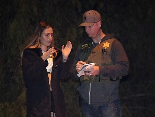 "Sheriff's deputy speaks to a potential witness as they stand near the scene Thursday, Nov. 8, 2018, in Thousand Oaks, Calif. where a gunman opened fire Wednesday inside a country dance bar crowded with hundreds of people on ""college night,"" wounding 11 people including a deputy who rushed to the scene. Ventura County sheriff's spokesman says gunman is dead inside the bar. (AP Photo/Mark J. Terrill)"