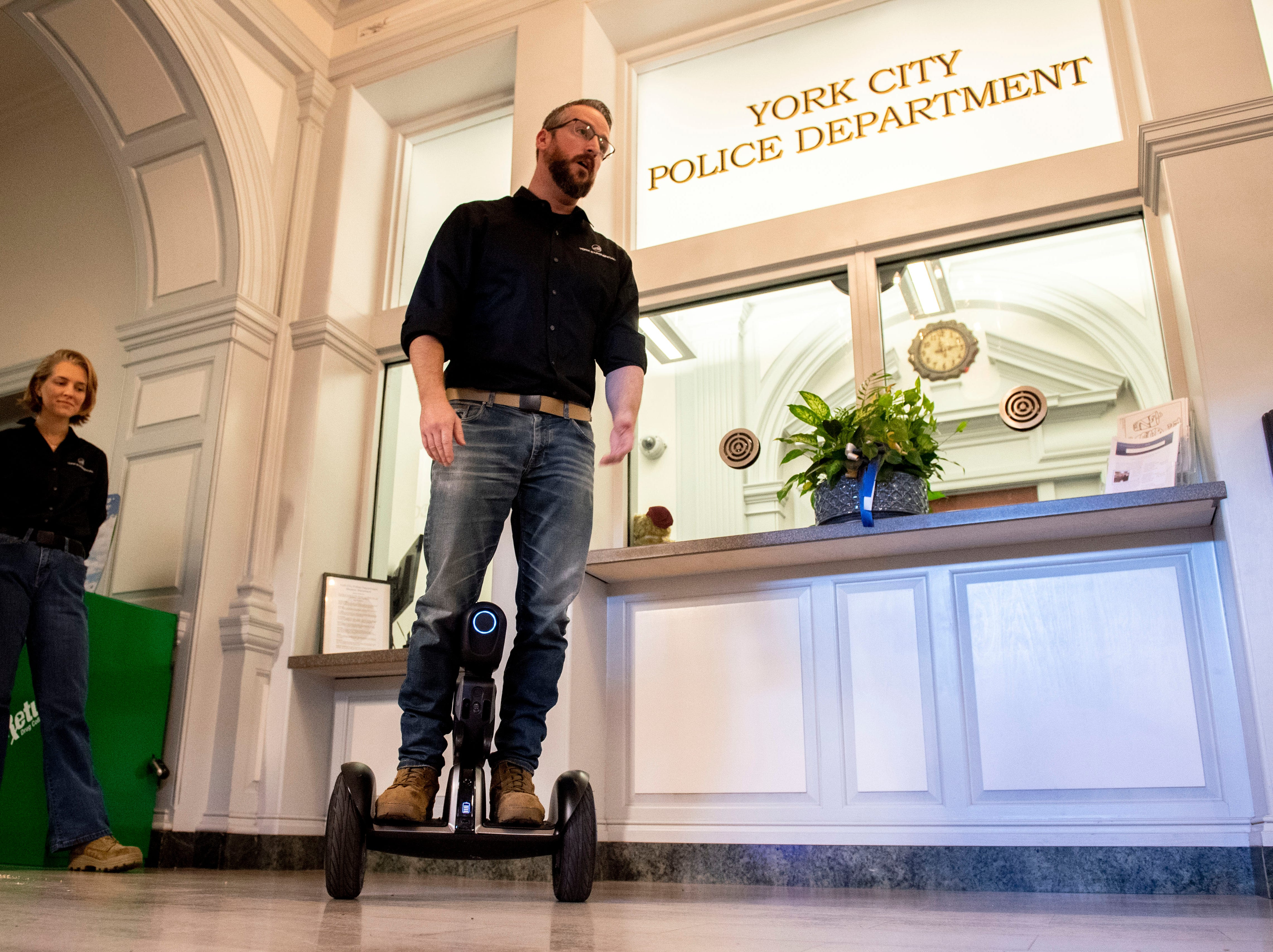 John McElligott, the CEO of York Exponential, rides the 'Loomo' during a demonstration of the robot at the York City Police Department on Thursday, Nov. 8, 2018.