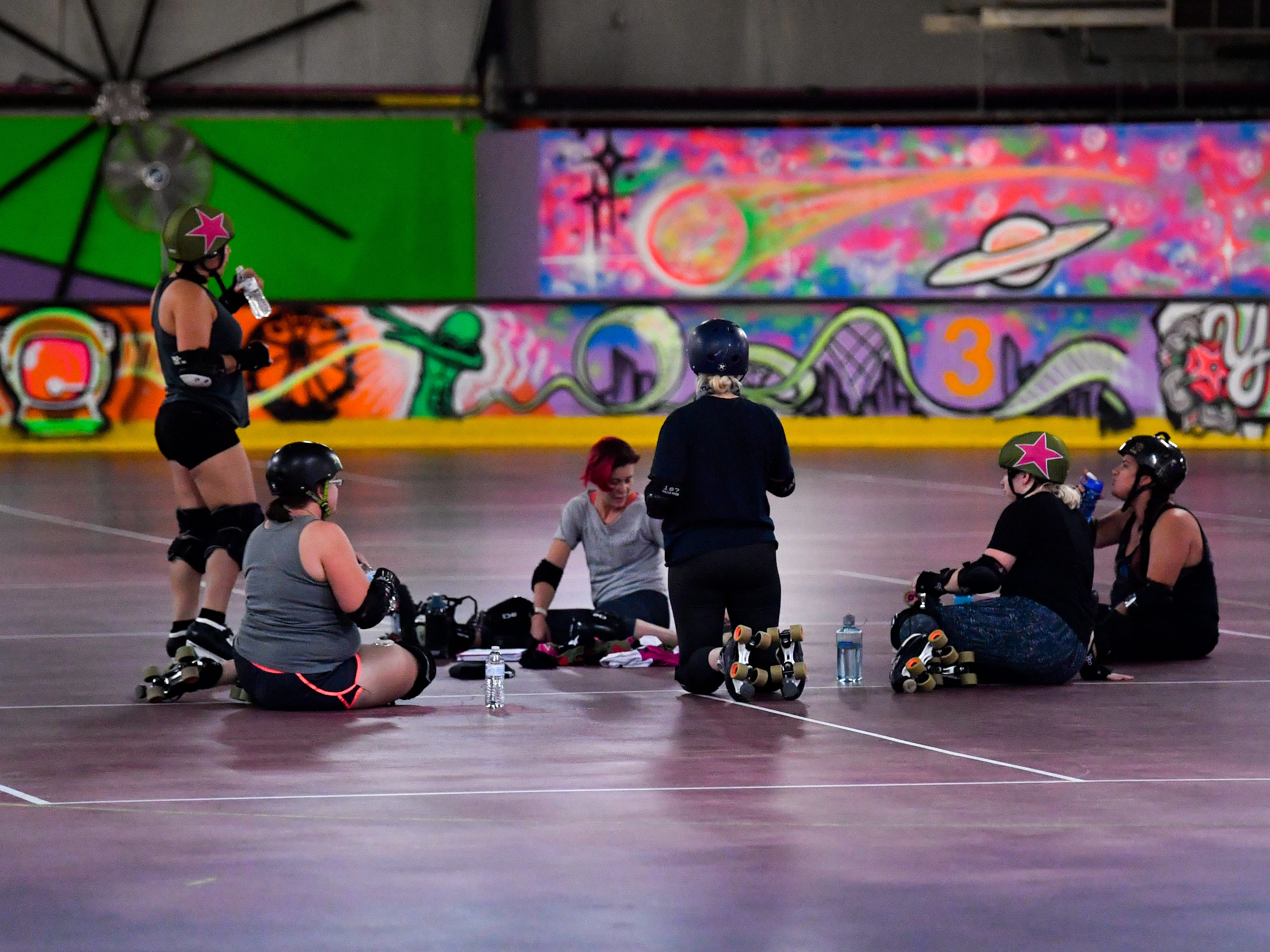 After a long and challenging practice, the Derby Dames convene in the middle of the rink for a water break before heading home, Thursday, October 18, 2018.