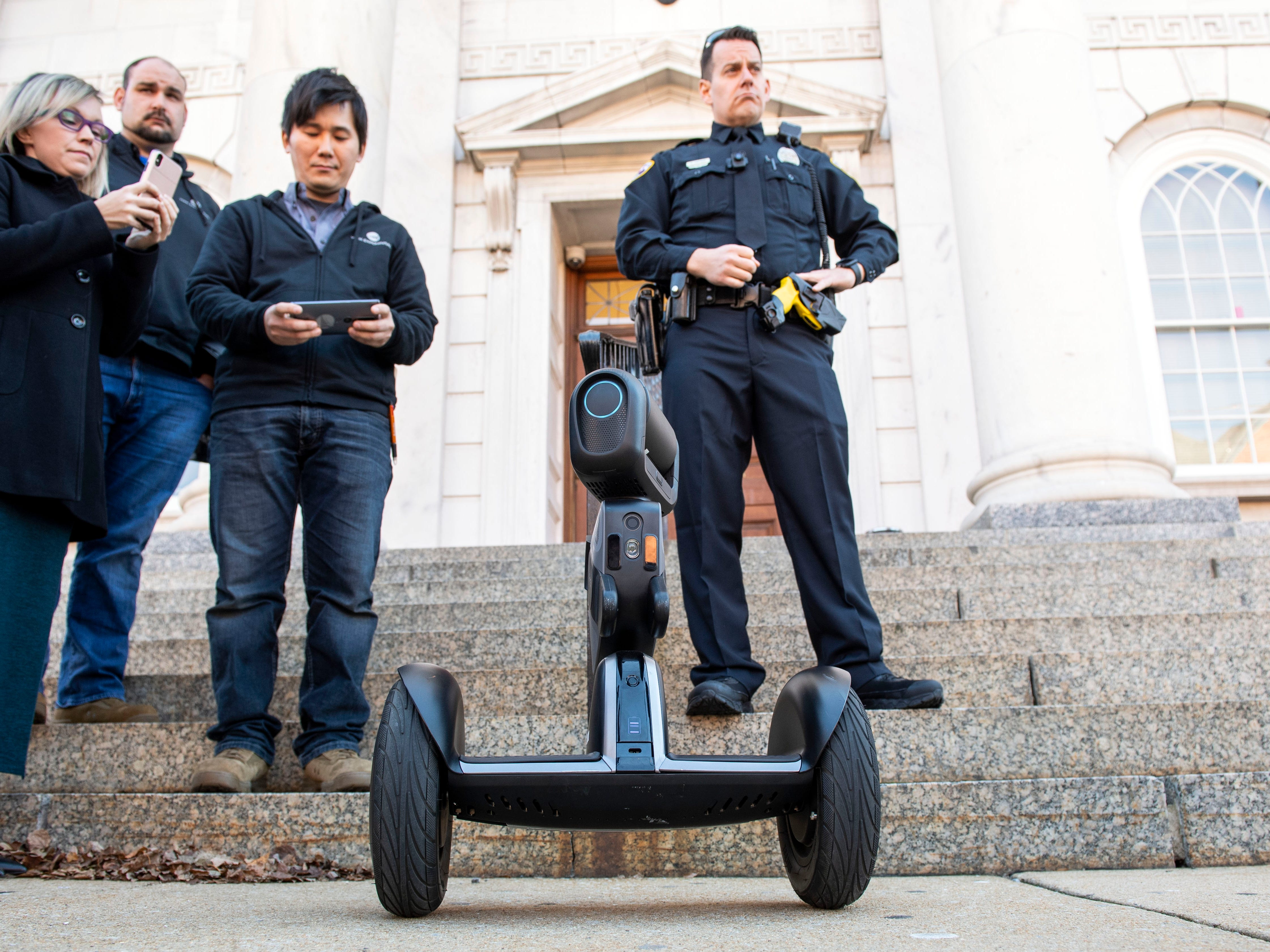 During a demonstration of the 'Loomo' Ñ a two-wheeled robot Ñ officer Derek Hartman, right, listens to York Exponential CEO explain features of the robot, Thursday, Nov. 8, 2018.