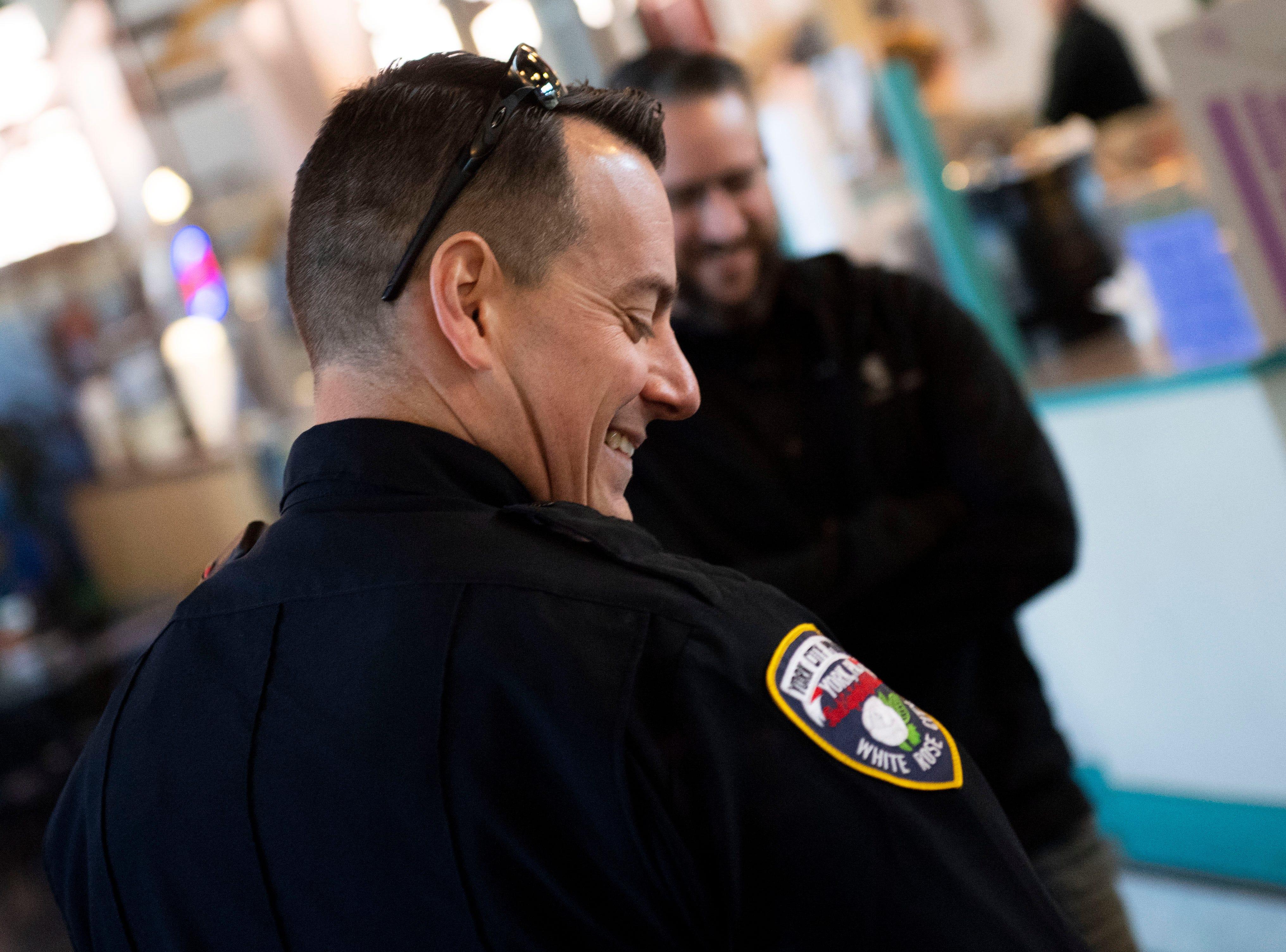 York City police officer Derek Hartman looks down at the 'Loomo' robot in Central Market, Thursday, Nov. 8, 2018.