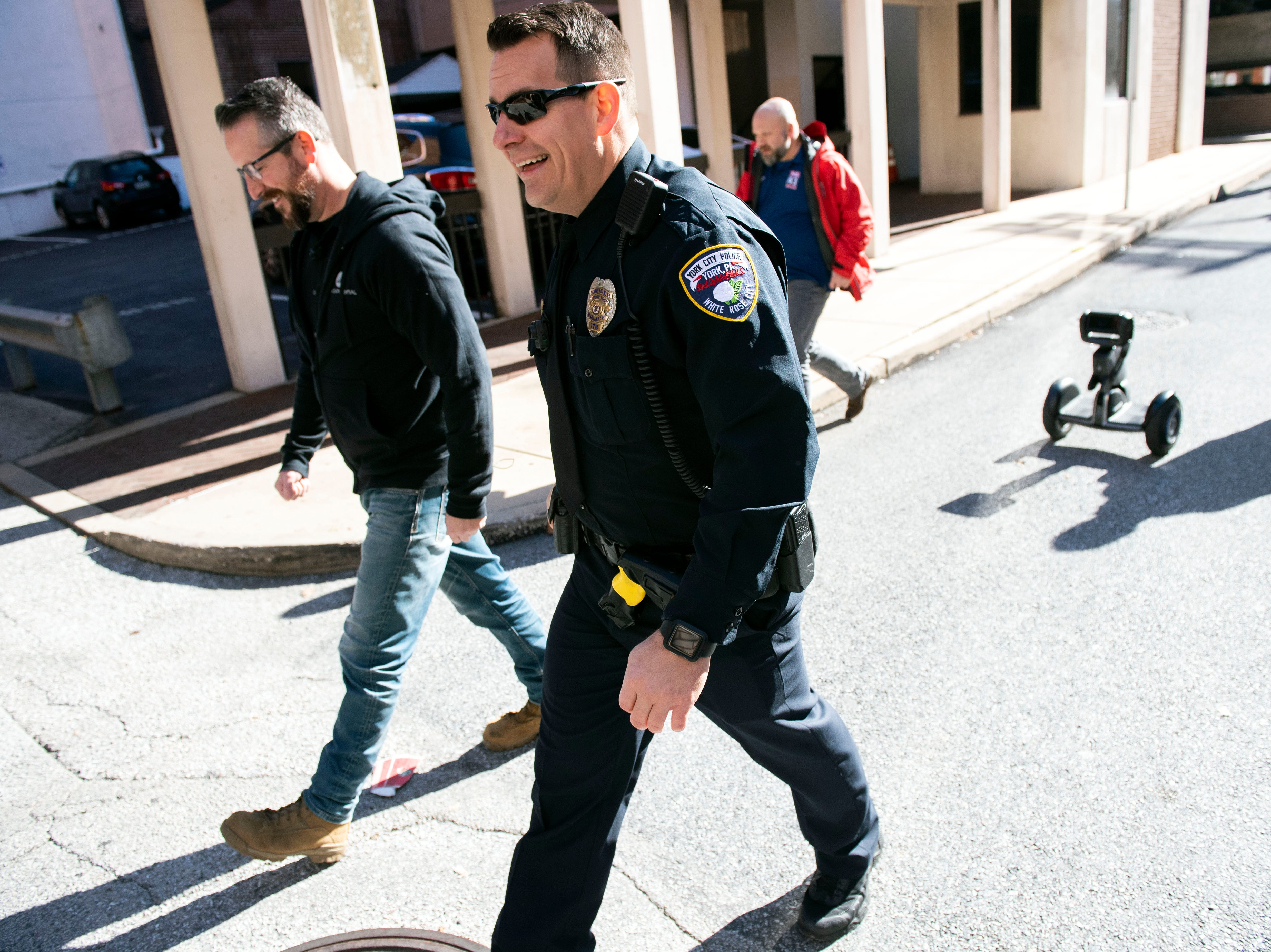 York Exponential CEO John McElligott, left, and York City Police Officer Derek Hartman walk toward Cherry Lane while the 'Loomo' follows behind. The two were trying out the robot, which could be used to help in city policing.