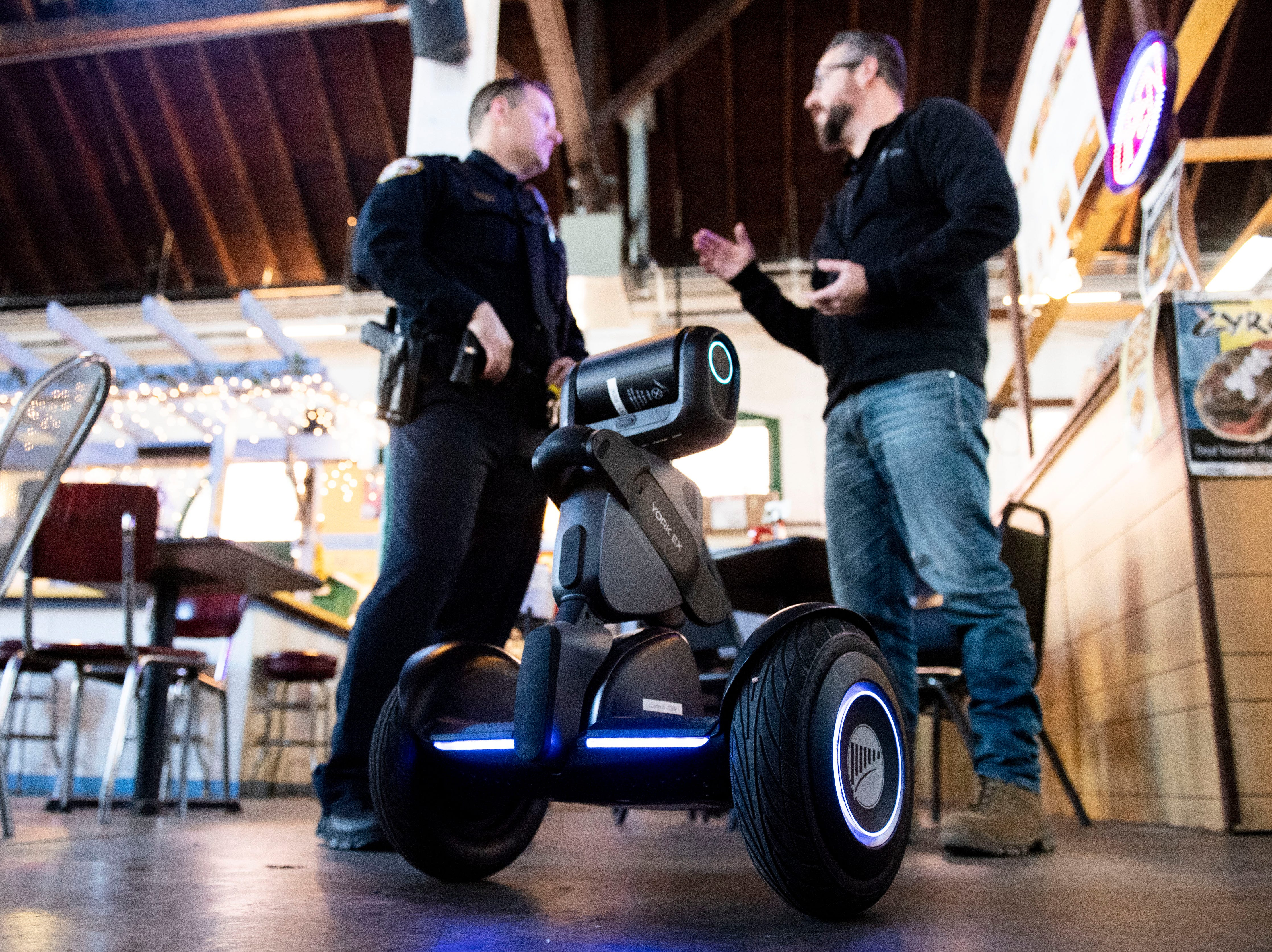 The 'Loomo' robot stands at attention in front of York City police officer Derek Hartman, left, and York Exponential CEO John McElligott in Central Market, Thursday, Nov. 8, 2018. McElligott believes the robot can be a valuable asset to the police department in the future.
