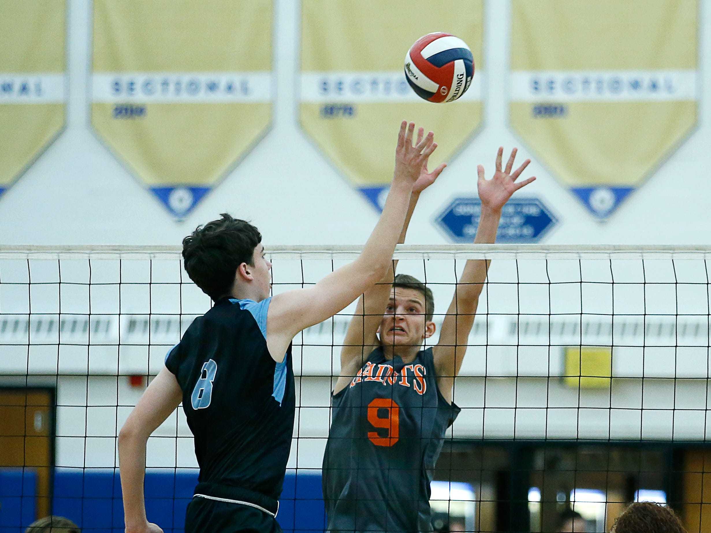 Class B volleyball final: Midlakes' Kyle McCann tips the ball over Churchville-Chili's Greg Czolgosz in the first set at Webster Schroeder High School.