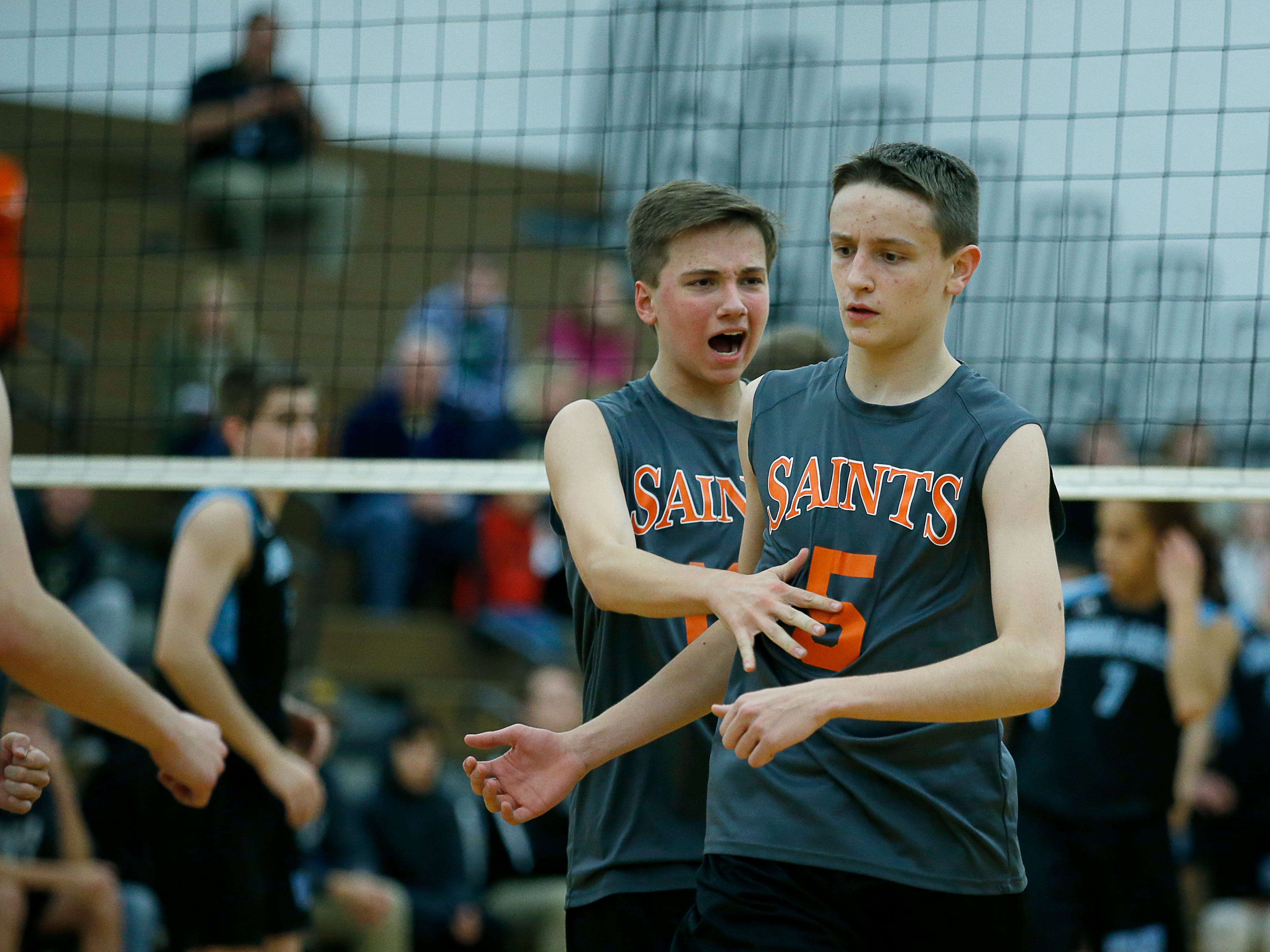 Class B volleyball final: Churchville-Chili's Joe Wollke reacts with teammate Griffin Stella after scoring for a 10-6 lead over Midlakes in the second set at Webster Schroeder High School.