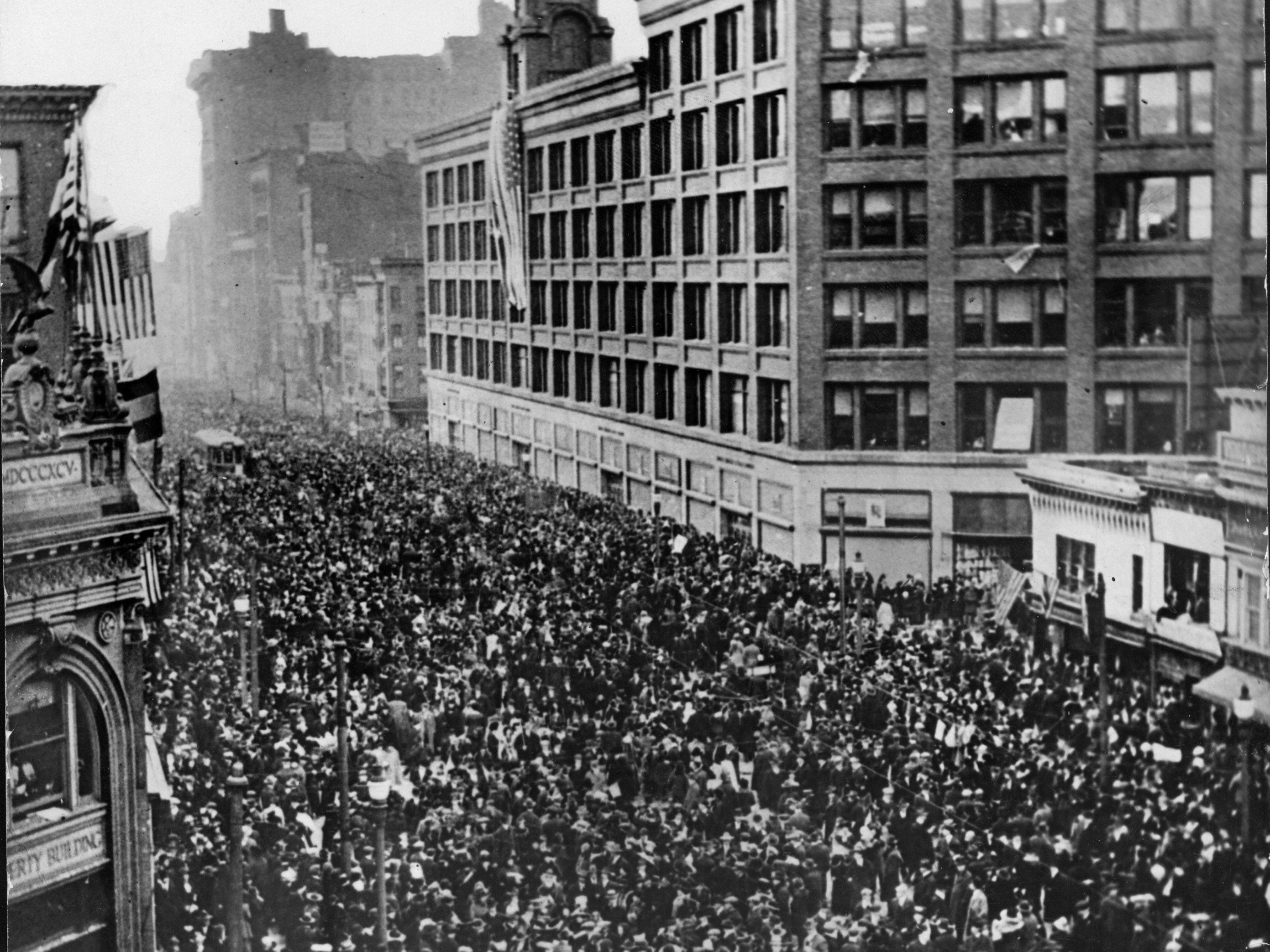 Crowds in Rochester celebrate the end of World War I on Armistice Day, Nov. 11, 1918. The Sibley Building is in the background.