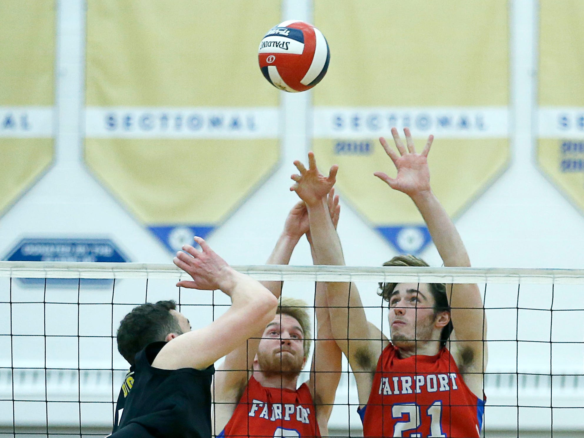 Class A volleyball final: Fairport's Kade Carlson and Matt Beiter defend against McQuaid's Brady Darby in the third set at Webster Schroeder High School.